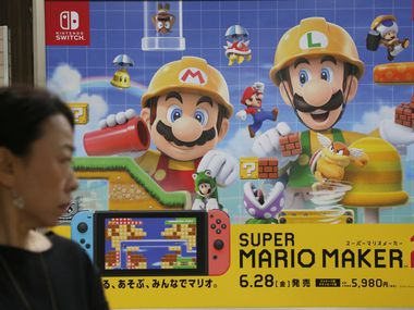 A woman walks by an advertisement poster of a Nintendo in Tokyo in Tokyo, Tuesday, July 9, 2019. Nintendo Co. says it plans to start making its Switch console in Vietnam this year, transferring some of its production from China. (AP Photo/Koji Sasahara)