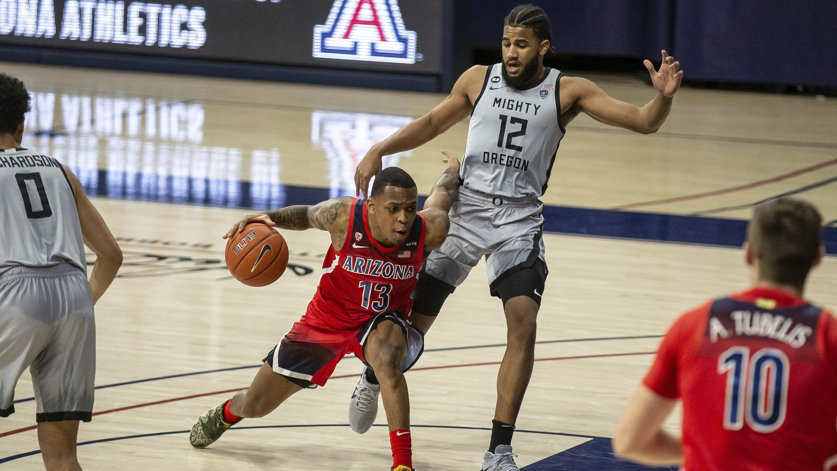 Arizona guard James Akinjo (13) moves the ball around Oregon guard LJ Figueroa (12) during an NCAA college basketball game, Saturday, Feb. 13, 2021, in Tucson, Ariz.