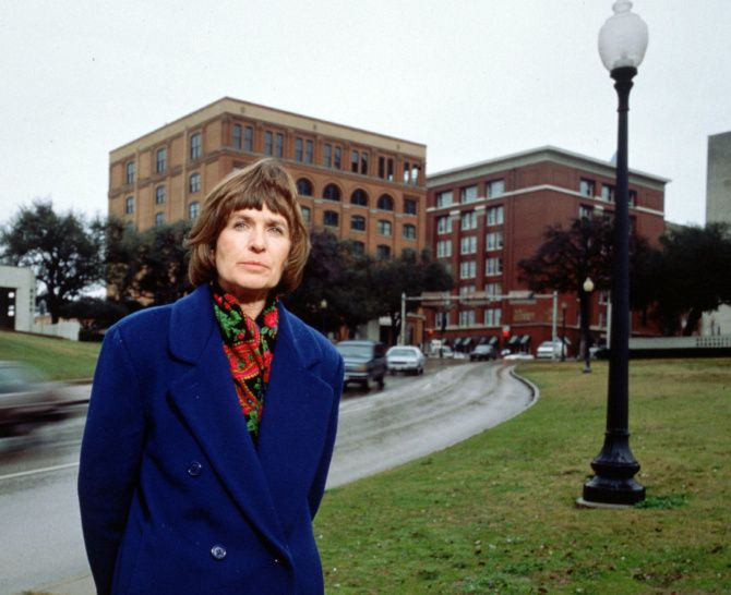 Marina Porter, standing by the grassy knoll across from the former Texas School Book Depository in 1993, is a retiree in Rockwall now.