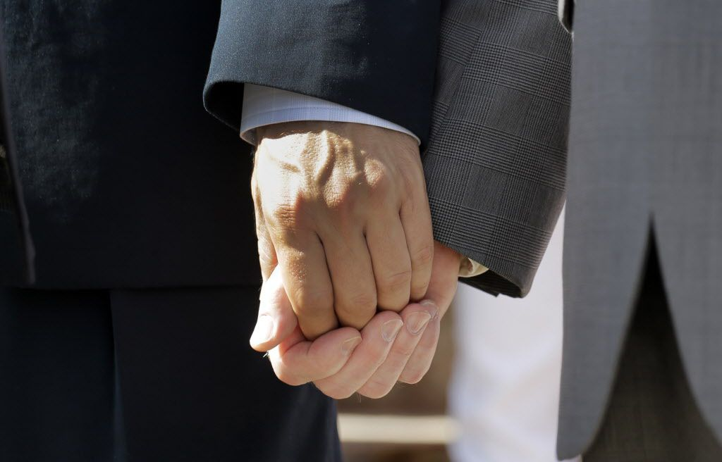 Texas marriage plaintiffs Vic Holmes, left, and partner Mark Phariss, right, hold hands on the steps of the Texas Capitol during a news conference on June 29.
