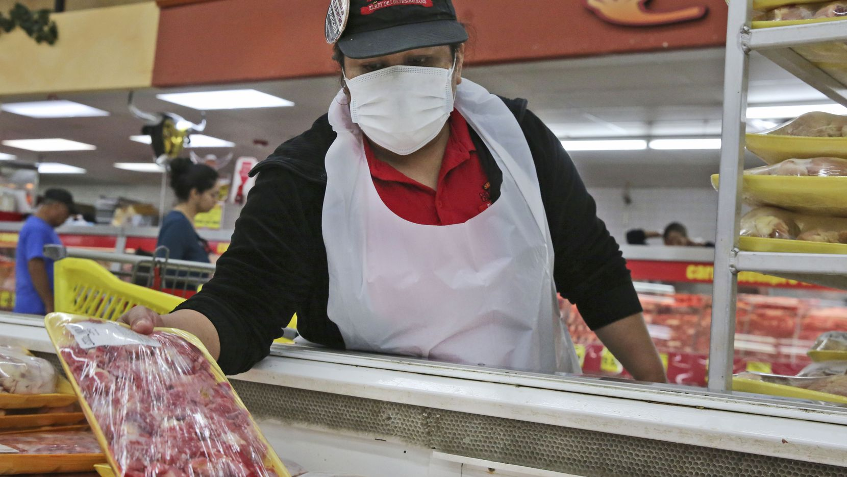 Marcela Martinez Salazar wears a mask while restocking at El Rancho grocery store in Dallas on March 26.