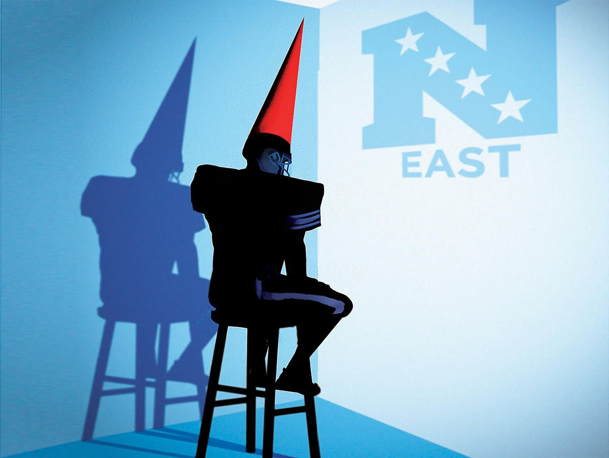 A man wearing dunce cap sits on a stool in a corner.
