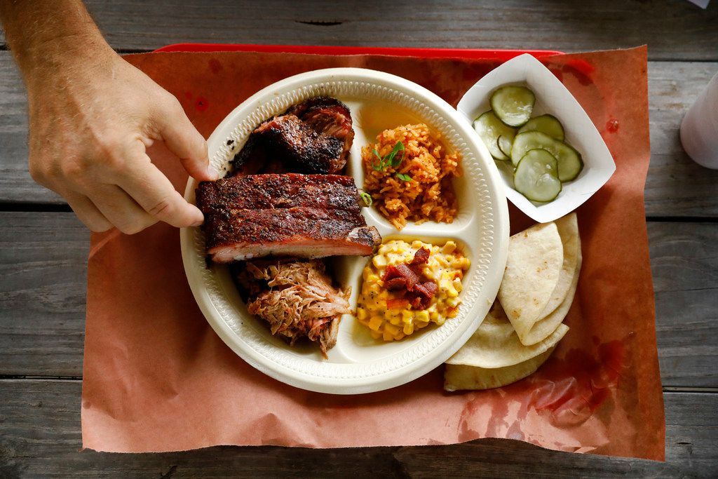 Pork ribs, pulled pork and brisket are served with a side of jalapeño corn, Spanish rice (only available on Saturdays), spicy pickles and homemade tortillas at Flores Barbecue in Whitney.
