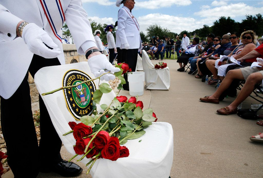 Jim Sammons of the Knights of Columbus places roses on an empty chair designated for the U.S. Army during a Memorial Day ceremony at Dallas-Fort Worth National Cemetery in Dallas on Monday.