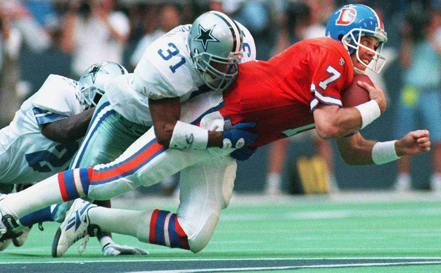 Cowboys safety Brock Marion (31) brings down Denver Broncos quarterback John Elway during the first half of their game at Texas Stadium on Sept. 10, 1995.