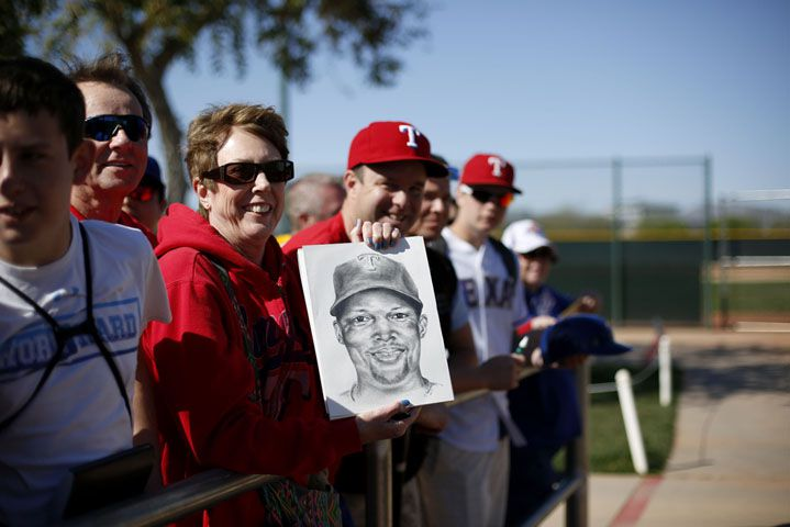 Texas Rangers fan Connie Goodwin, of Carrollton, Texas, holds up a drawing she made of third baseman Adrian Beltre, which she hopes Beltre will sign with his autograph, during a workout at the Rangers spring training facility in Surprise, Arizona Thursday March 5, 2015. (Andy Jacobsohn/The Dallas Morning News)