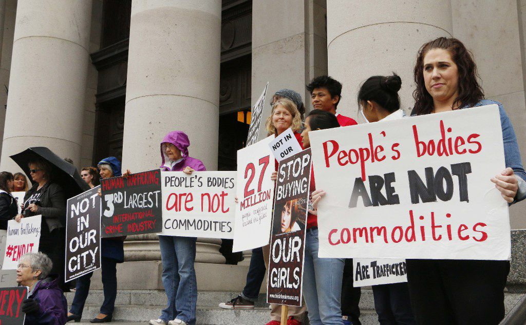 People opposed to child sex trafficking rally outside of the Washington state Supreme Court on Tuesday, Oct. 21, 2014,