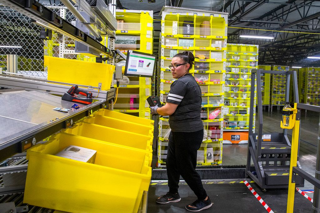 Elizabeth Moran picks up a package from a robot-delivered pod at an Amazon fulfillment center in Coppell.