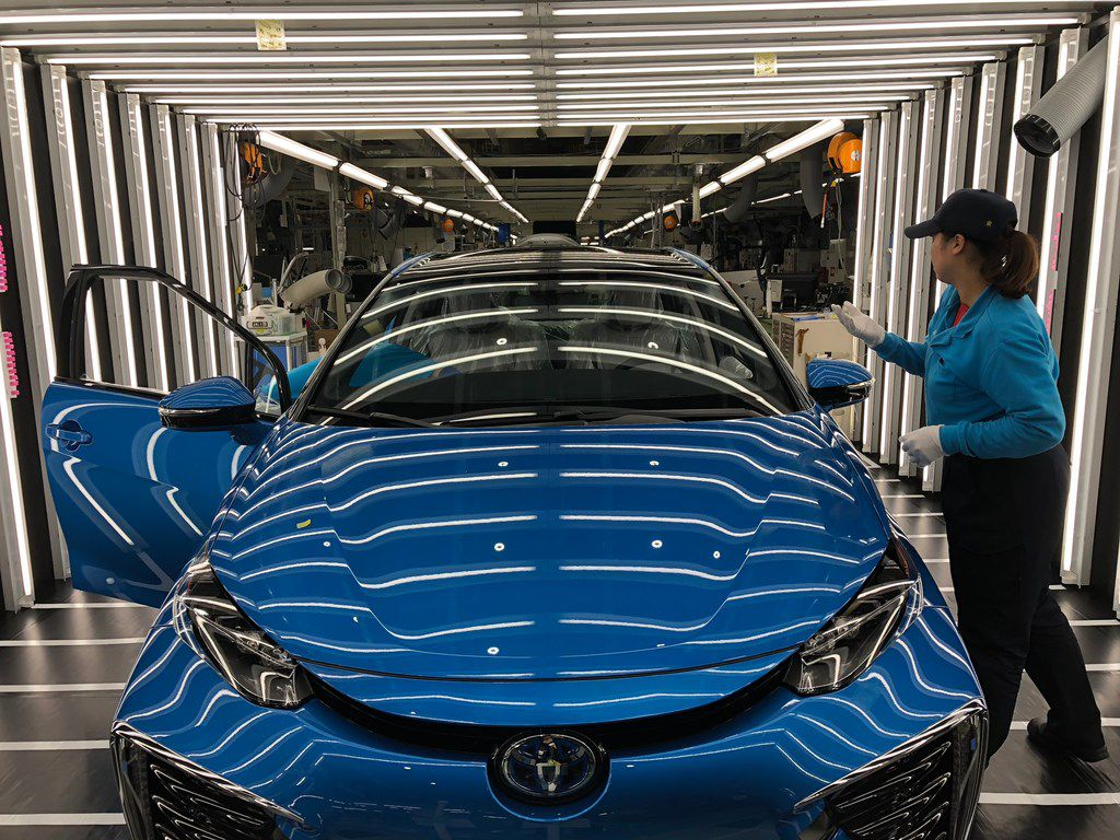 Workers putting the finishing touches on a car at Toyota's factory in its Japanese hometown, Toyota City.