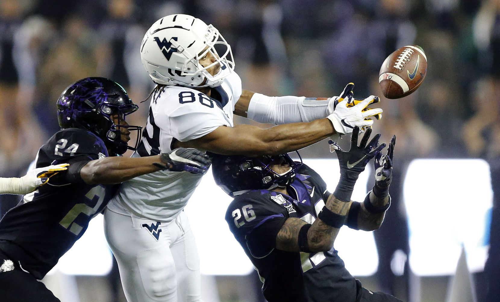 TCU Horned Frogs safety Vernon Scott (26) looks to pick off a tipped pass to West Virginia Mountaineers wide receiver Isaiah Esdale (88) at Amon G. Carter Stadium in Fort Worth, Friday, November 29, 2019. The pass fell incomplete but the Mountaineers picked up the late fourth quarter first down on a targeting call. The Horned Frogs lost, 20-17.