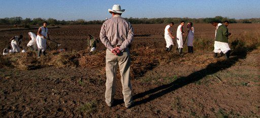 Then-Clemens Unit Warden Terry Foster watches Youthful Offender Program inmates work the fields outside of the prison in Brazoria on Dec. 5, 1999.