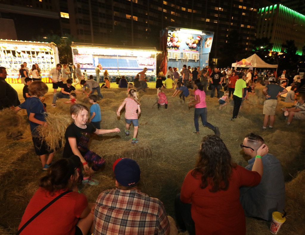 Families play in the hay while bands perform during the Old97's County Fair at Main Street Garden in Dallas, TX, on Apr. 8, 2017. (Jason Janik/Special Contributor)