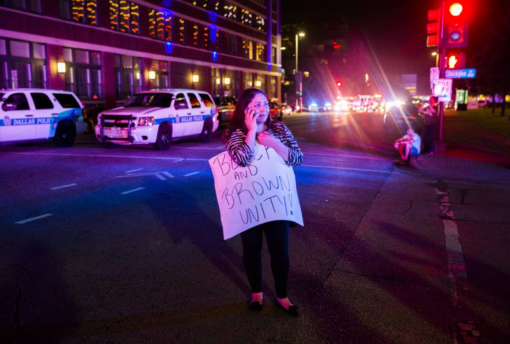 A woman makes a phone call holding a protest sign at the intersection of S Lamar and Jackson St after gunmen shot 11 people during a Black Lives Matter protest on Thursday, July 7, 2016 in downtown Dallas, Texas.  (Ashley Landis/The Dallas Morning News)