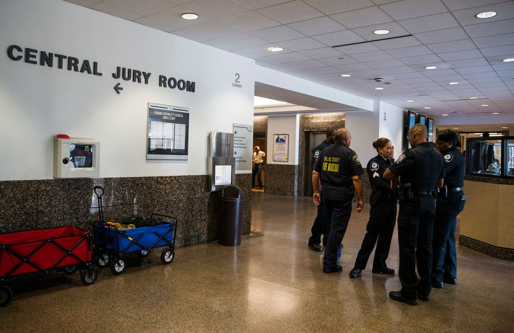 A Fire Marshall talks with security guards in the hallway outside the Central Jury Room as potential jurors are selected for the Amber Guyger trial on Friday, September 6, 2019 at the Frank Crowley Courts Building in Dallas. Reporters were not allowed inside the room. (Ashley Landis/The Dallas Morning News)