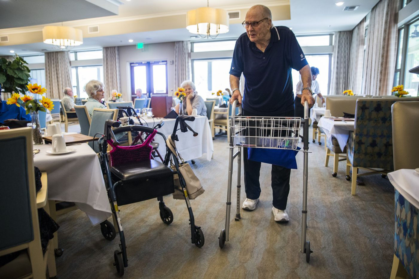 Bob Stiegler greets other residents in the dining room after eating lunch at The Village at Mapleshade in Plano this month.