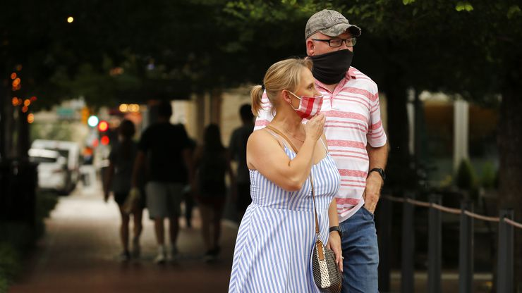 """As three single-day records related to coronavirus were set Thursday, Abbott acknowledged that the statewide mask order he issued last week is unpopular. But he said people simply must become familiar with """"the severity of COVID-19 right now"""" in Texas and, like the people shown walking in downtown Fort Worth last week, wear masks."""
