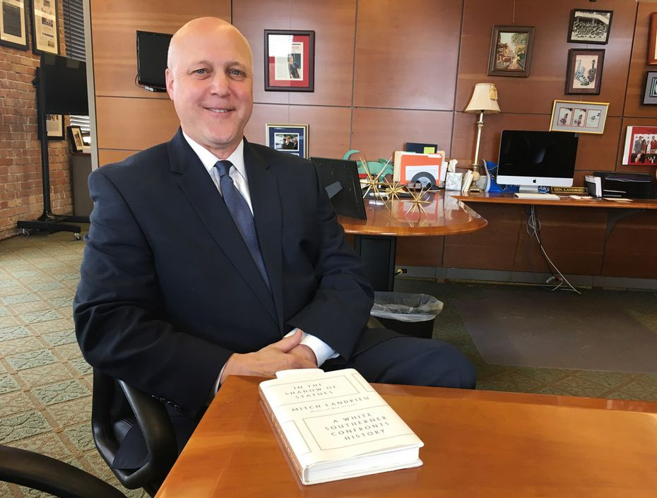 "New Orleans Mayor Mitch Landrieu poses with a copy of his new book, ""In the Shadow of Statues"" in New Orleans in March. The book is a memoir in which Landrieu discusses the issues of race that affected his personal and political life, and his role in the removal of four Confederate-related monuments from the city landscape."