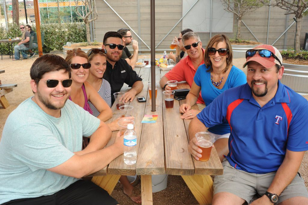 Friends enjoy brews, music, and cars at the custom car show at Texas Ale Project in Dallas, TX on August 15, 2015.