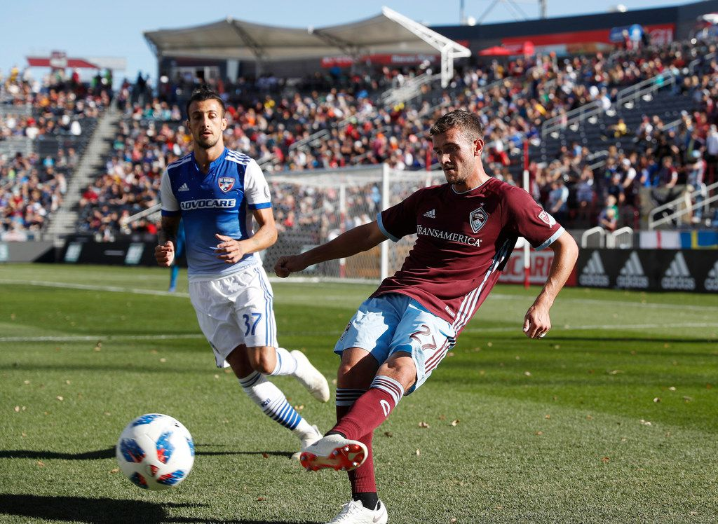 Colorado Rapids defender Deklan Wynne, front, passes the ball as FC Dallas forward Maximiliano Urruti comes in to cover in the first half of an MLS soccer match Sunday, Oct. 28, 2018, in Commerce City, Colo. (AP Photo/David Zalubowski)