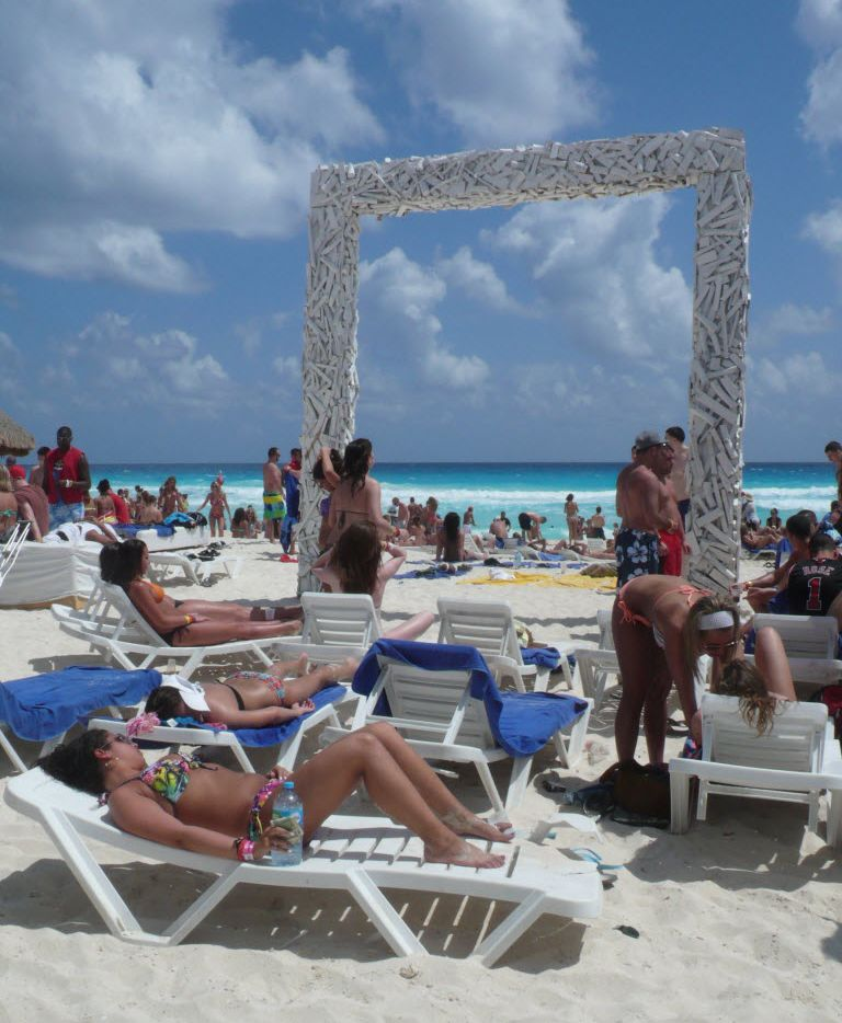 Sunbathers gather along the beach in Cancun.  The resort area has been the site of increased violence, though tourists have largely been spared its effects.