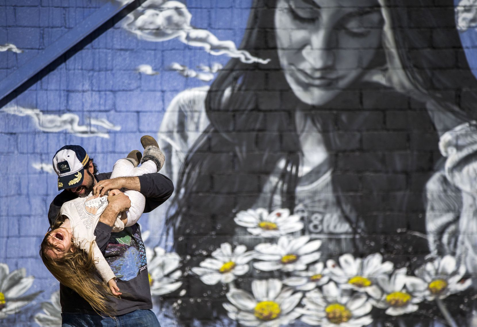 Three-year-old Maryella Woodstock Most is tickled by her father, Johnny Woodstock, in an outdoor area at Deep Ellum Art Company in Dallas on Sunday, March 3, 2019. Woodstock said they recently moved to Dallas from New Orleans. (Daniel Carde/The Dallas Morning News)