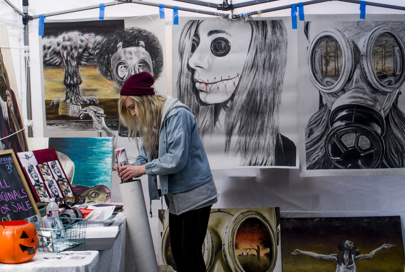Artist Jamie Rachel organizes the artwork in her booth at ArtsGoggle in 2018. This year's street fair is Oct. 19.
