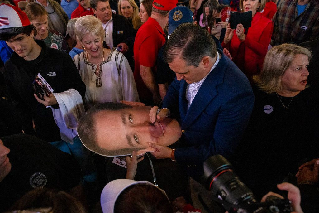 Senator Ted Cruz signs a cutout of his head following his campaign rally at The Fort Worth Herd on Friday, October 19, 2018.