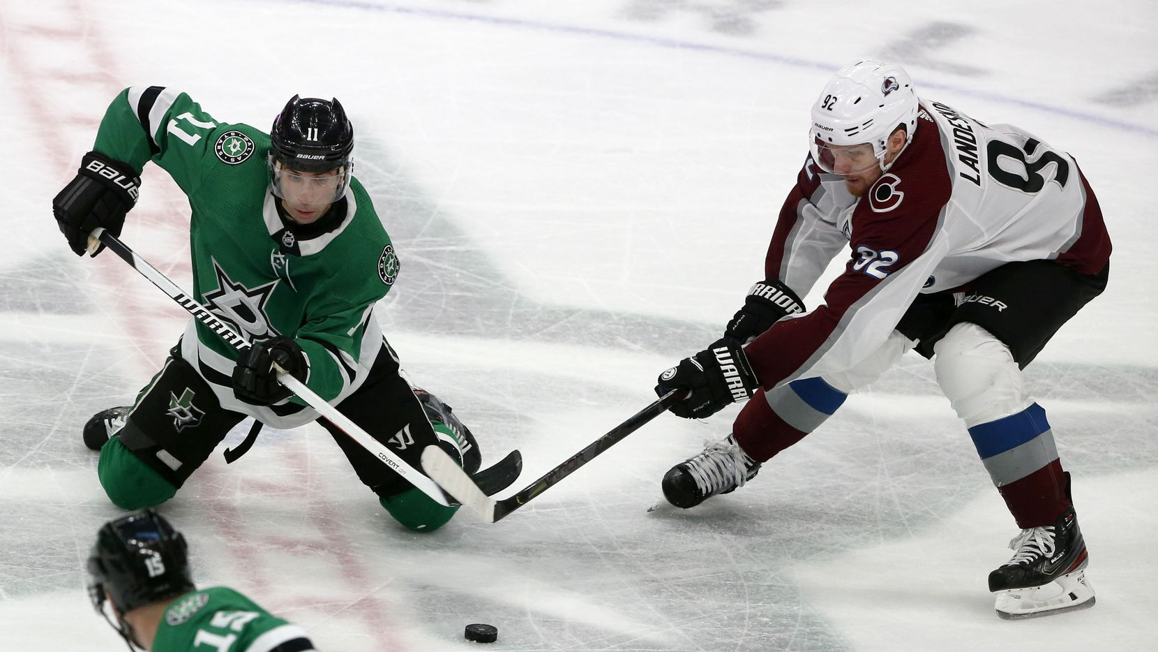 Dallas Stars center Andrew Cogliano (11) and Colorado Avalanche left wing Gabriel Landeskog (92) battle for the puck during the third period of an NHL hockey game in Dallas, Saturday, Dec. 28, 2019.