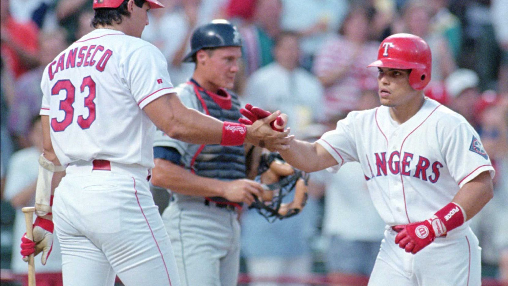 Former Rangers teammates Jose Canseco (left) and Ivan Rodriguez