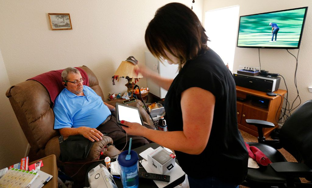 Former Dallas Cowboy George Andrie tries to connect a new pair of bluetooth ear buds with the help of his daughter, Mary Brooks, at his home in Woodway, Texas on Sunday, April 9, 2017.  (Tom Fox/The Dallas Morning News)