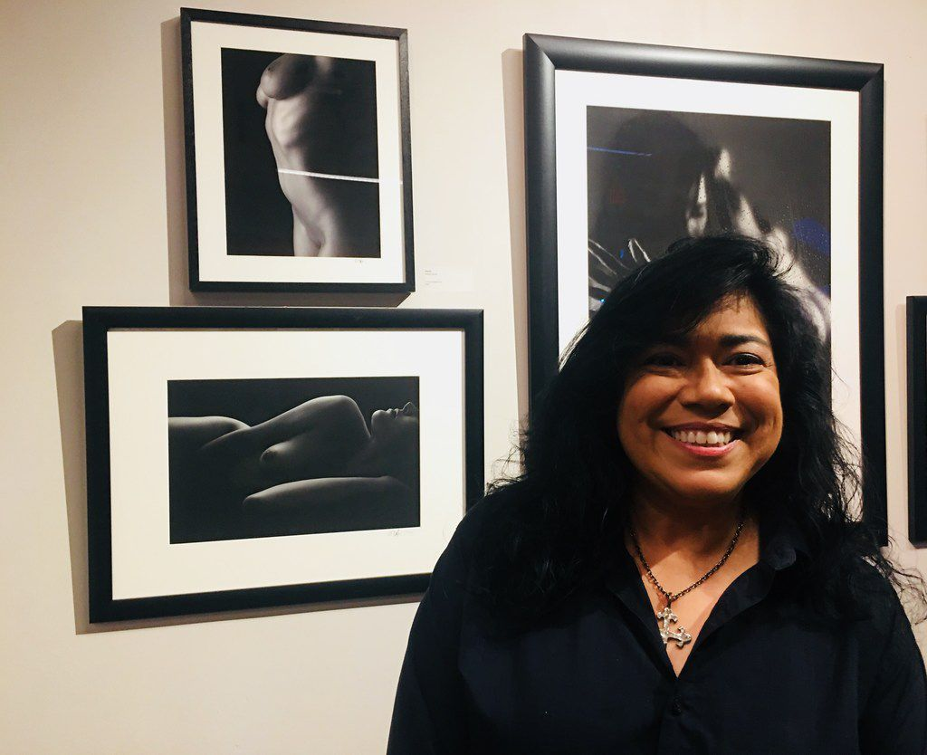 The photographer Debra Gloria poses with her photos during the art show MaricónX featuring Hispanic LGBT artists at the Oak Cliff Cultural Center on May 4.