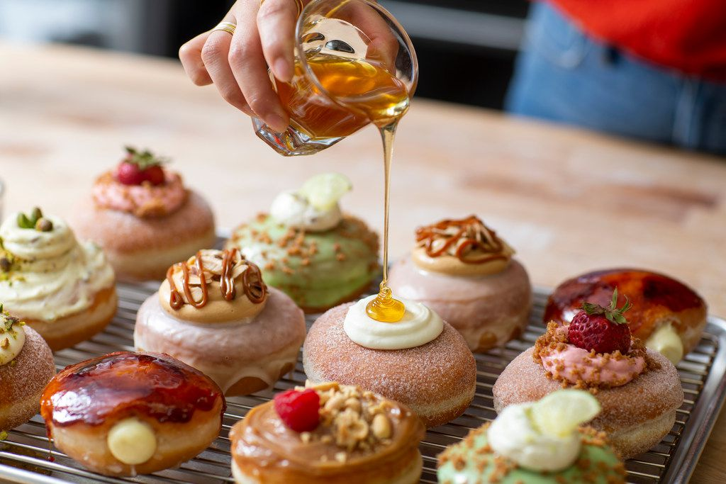Detour Doughnuts and Coffee owner Jinny Cho tops off a cream-filled doughnut with a dollop of honey at her Frisco store..