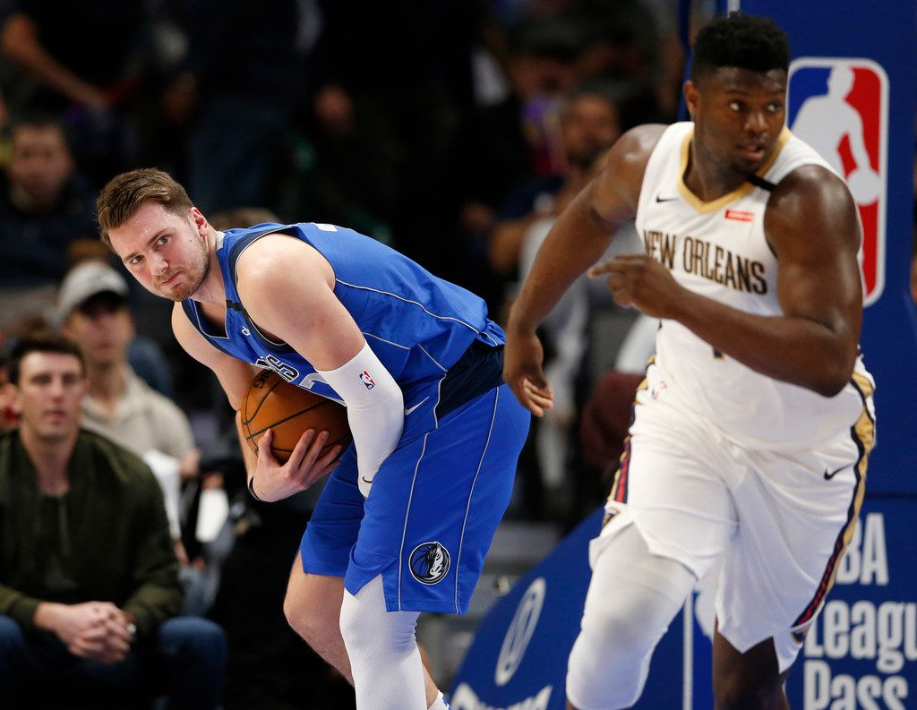 Dallas Mavericks guard Luka Doncic (77) grimaces after getting hit in the hand as he grabs a rebound during the first quarter of play at American Airlines Center in Dallas on Wednesday, March 4, 2020. New Orleans Pelicans forward Zion Williamson (1) makes his way up the court.