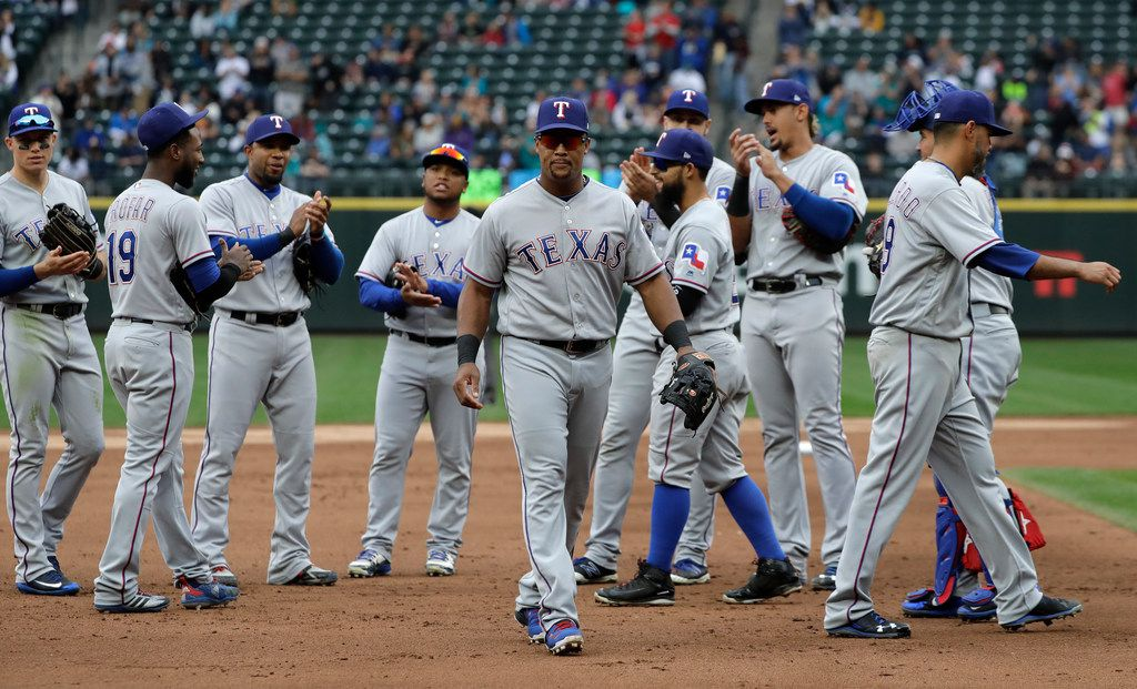 Texas Rangers' Adrian Beltre, center, is applauded by teammates as he walks off the field during the fifth inning of a baseball game against the Seattle Mariners after he was replaced by Jurickson Profar at third base, Sunday, Sept. 30, 2018, in Seattle. (AP Photo/Ted S. Warren)