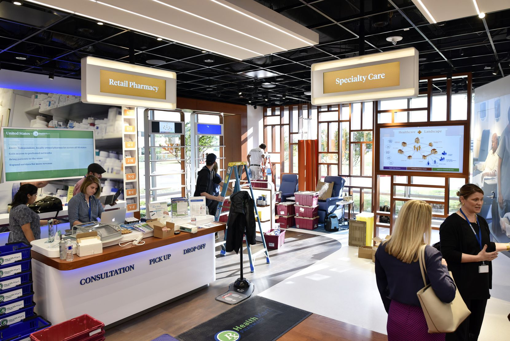 McKesson employees and construction workers prepare the company's Vision Center for the grand opening of the new McKesson offices in Irving,. The museum-like display is used to  educate clients and employees about company operations.