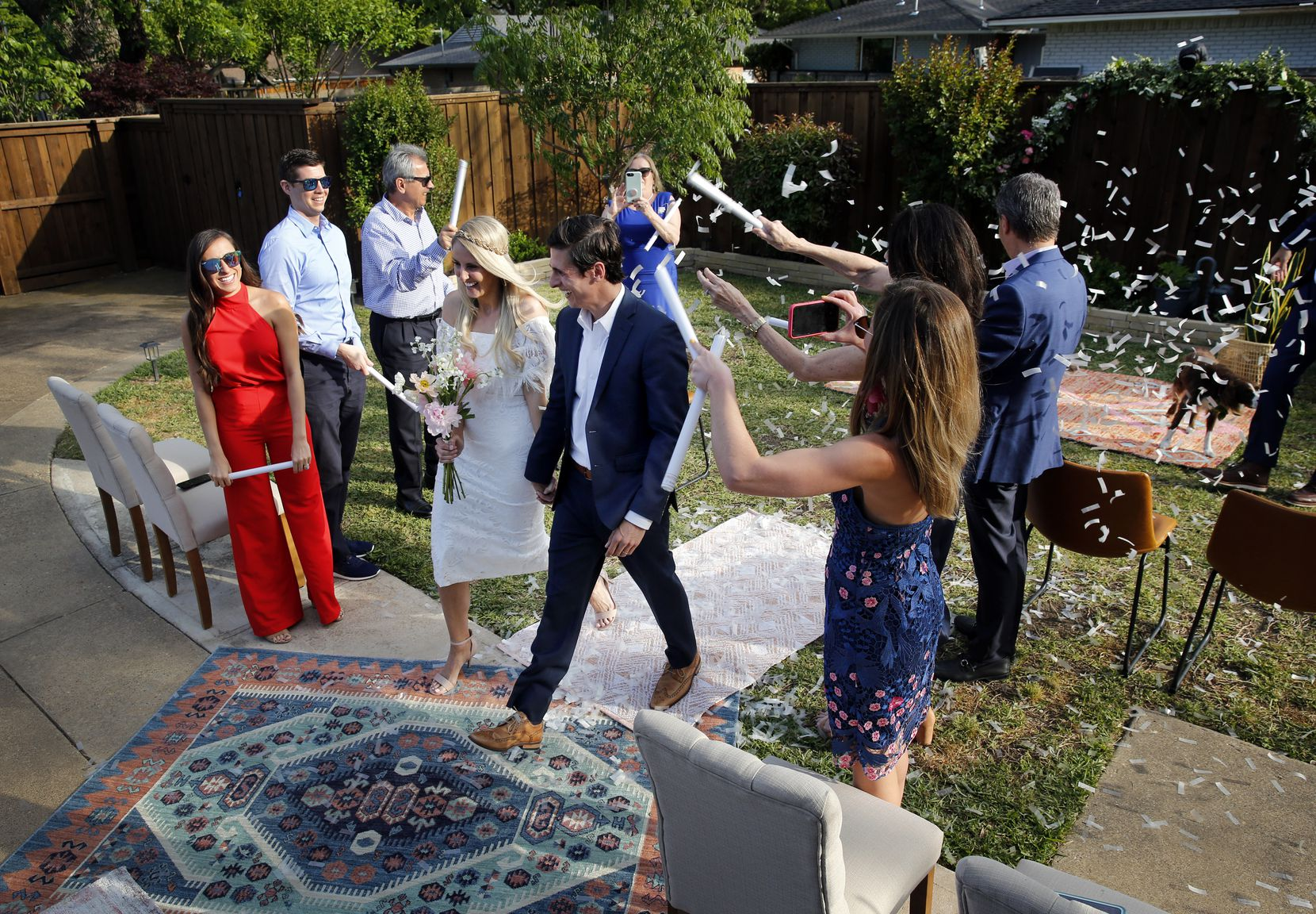 After tying the knot, newlyweds Dana and Andrew Houshian walk down the carpeted aisle as family members toss confetti in the backyard of their northeast Dallas home.