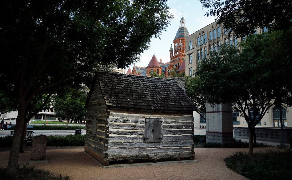 A replica of John Neely Bryan Cabin is pictured in Founders Plaza on Elm Street in downtown Dallas. The Old Red Courthouse rises above the cabin.
