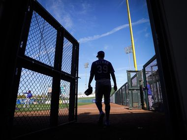 Texas Rangers starting pitcher Kolby Allard walks from the tunnel onto the field for the Rangers first a spring training game against the Kansas City Royals at Surprise Stadium on Friday, Feb. 21, 2020, in Surprise, Ariz.
