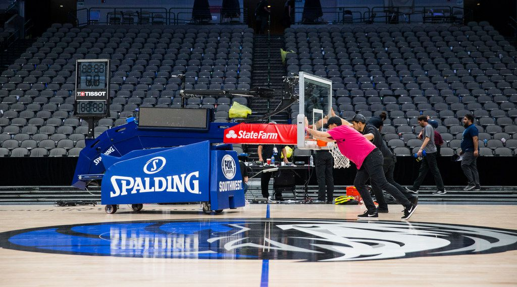 FILE - Crews remove a basketball hoop from the court after the Mavericks beat the Denver Nuggets 113-97 on March 11, 2020, at American Airlines Center in Dallas. During the game, the NBA suspended its season due to the spread of the new coronavirus.