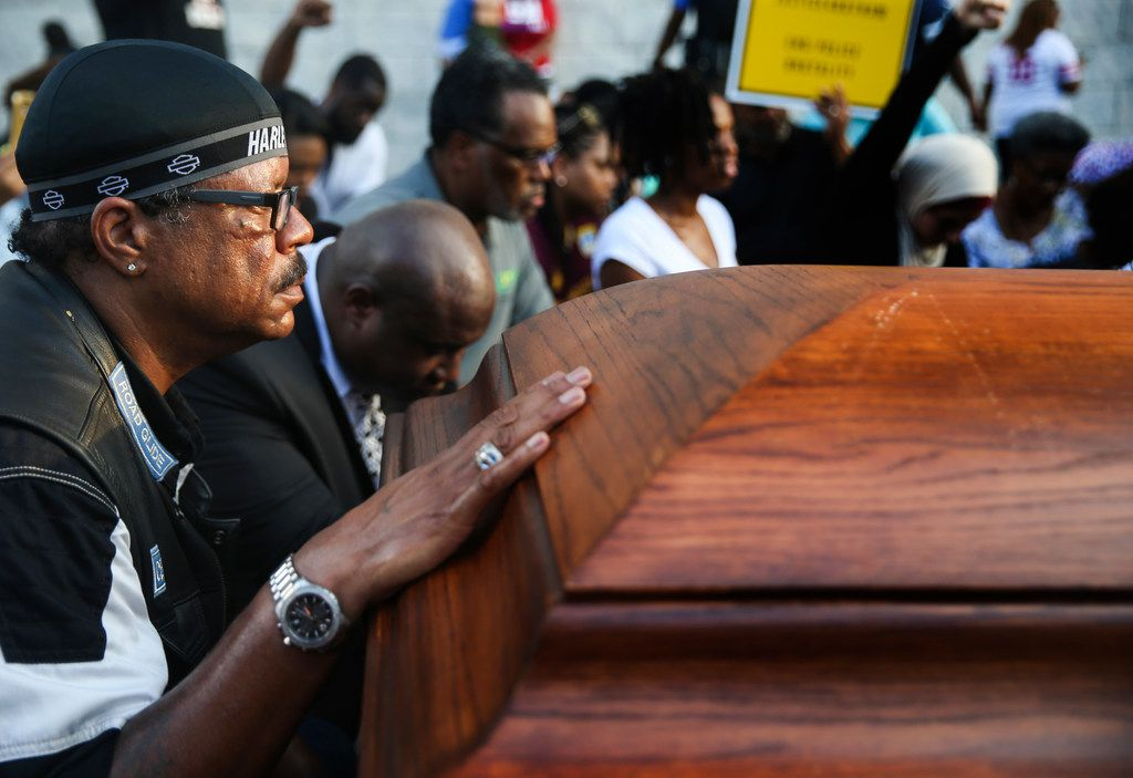 Milton Perkins of Dallas kneels at the foot of two empty coffin outside AT&T Stadium.
