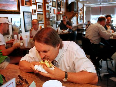 Soon, Al's Hamburgers will leave its home of 31 years, at Collins Street and NE Green Oaks Boulevard. (Before that, it was on another part of Collins Street for 29 and a half years.) In this 1997 file photo, Vick Langford takes a bite of a burger at the beloved Arlington restaurant.
