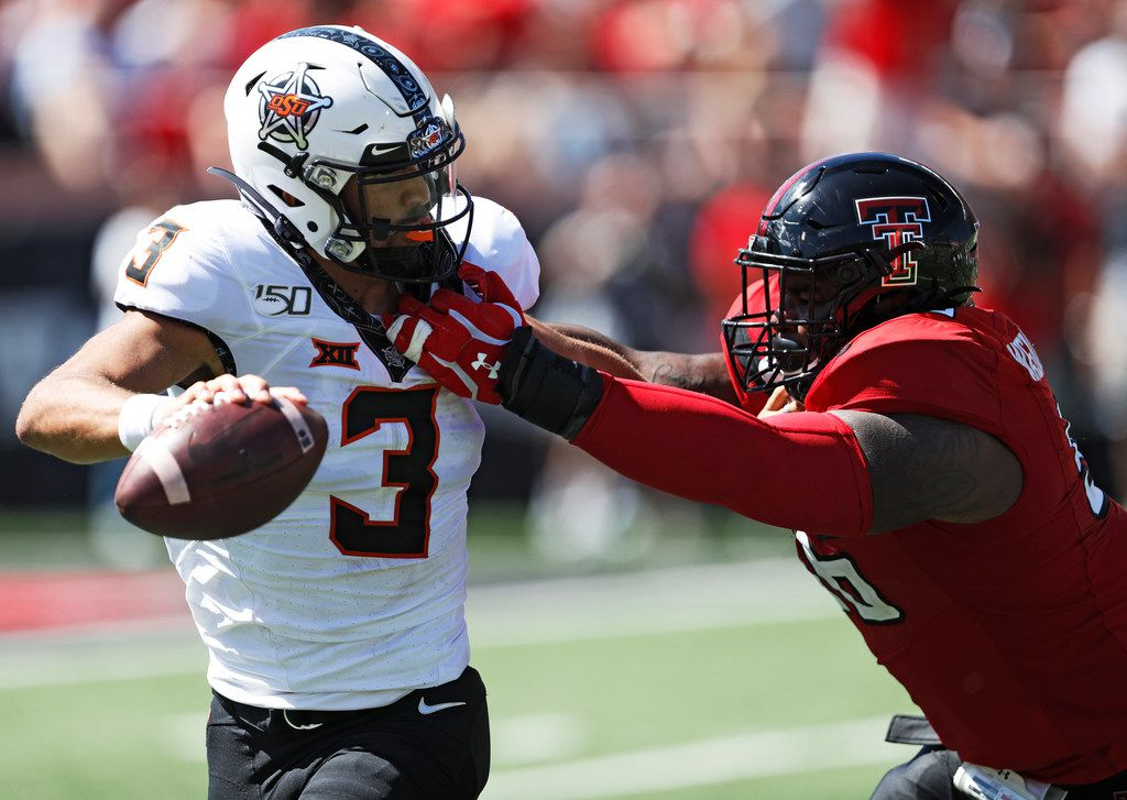 Oklahoma State's Spencer Sanders (3) is tackled by Texas Tech's Broderick Washington Jr. (96) during the second half of an NCAA college football game Saturday, Oct. 5, 2019, in Lubbock, Texas. (AP Photo/Brad Tollefson)