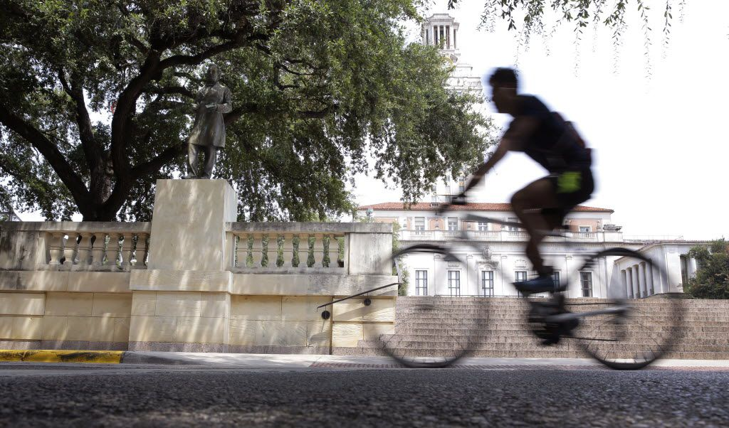 A cyclist passes a statue of Confederate President Jefferson Davis on the University of Texas campus, Thursday, Aug. 27, 2015, in Austin, Texas. University of Texas officials are asking an Austin judge to let them move the century-old statue from central campus, but the Sons of Confederate Veterans, which says it seeks to celebrate Southern heritage, wants Davis to stay where it is. (AP Photo/Eric Gay)