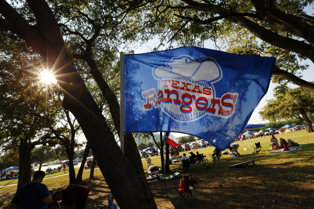 A Texas Rangers flag bears the original team logo as fans tailgate before the ALDS Series game between Texas Rangers and Toronto Blue Jays at Globe Life Park in Arlington, Sunday October 11, 2015.