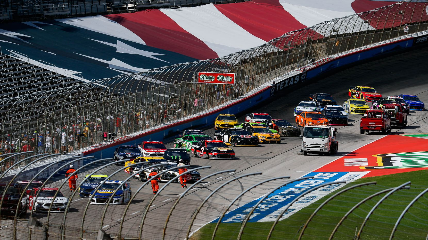 Fans line the fence to get photos of the stalled cars during the NASCAR Cup Series O'Reilly Auto Parts 500 race on July 19, 2020 at Texas Motor Speedway in Fort Worth. The race was the first major league sporting event in Texas open to fans amid the pandemic.