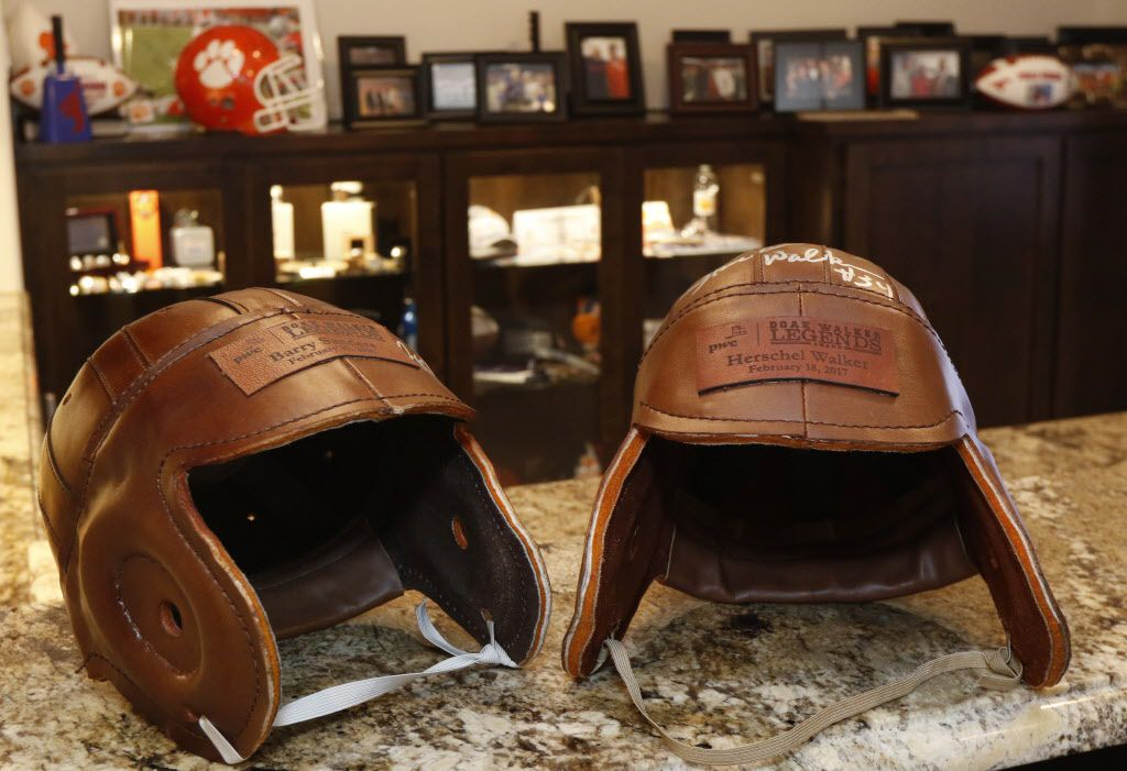 Leather football helmets signed by Barry Sanders, left, and Herschel Walker are part of SMU head football coach Chad Morris's recruitment room in his home in Highland Park, Texas on Friday, June 23, 2017. (David Woo/ The Dallas Morning News) sportsmagsmuphoto