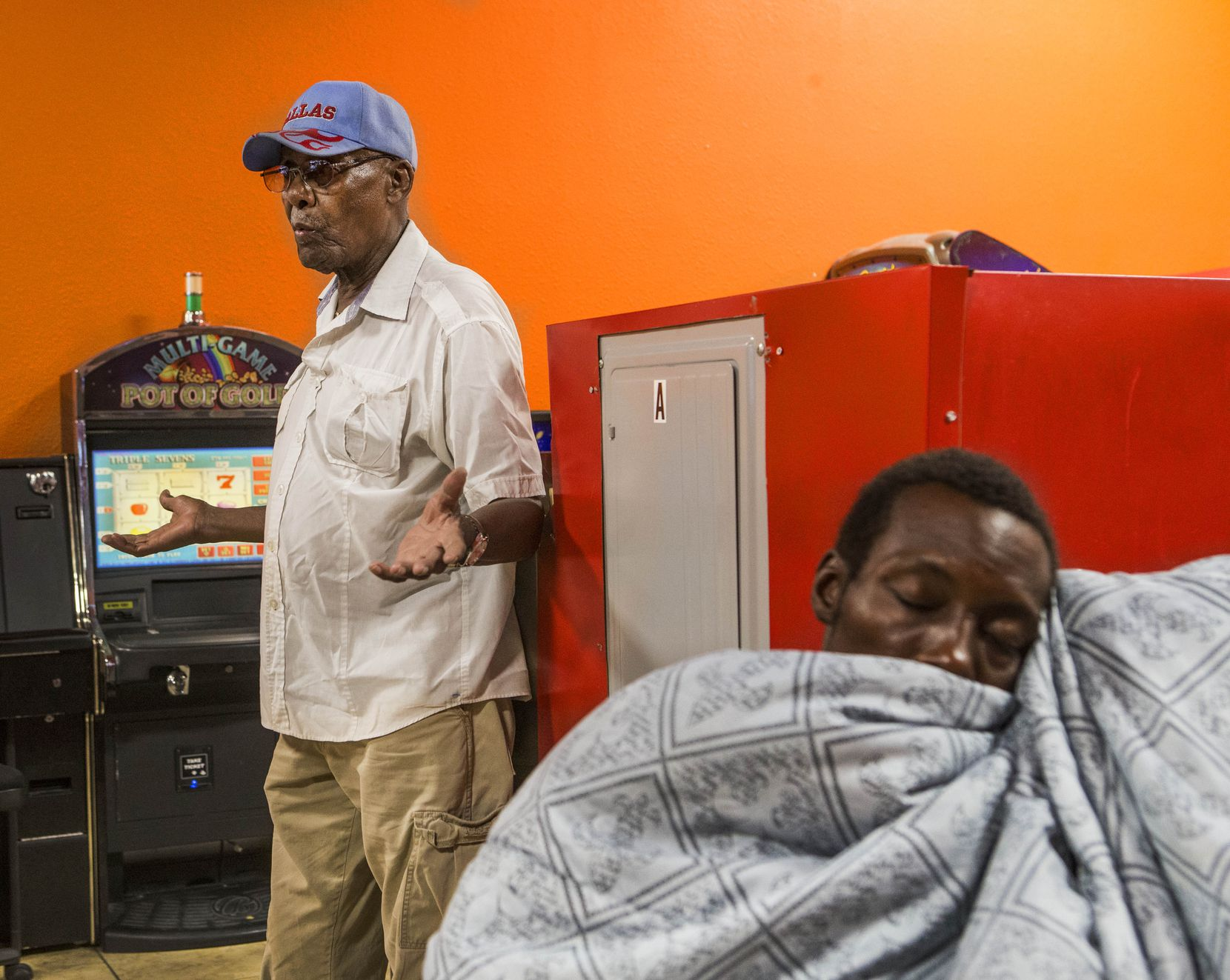 Longtime Dallas resident Elijah Hawkins, left, talks about the news regarding former Dallas Mayor Pro Tem Dwaine Caraway as Tae Shelton, of Dallas, takes a nap at Amigo Wash & Dry in Dallas on Aug. 9, 2018. Hawkins said he was disappointed to hear about Caraway, who will plead guilty to federal corruption charges. He knew him to be approachable and invested in the community.