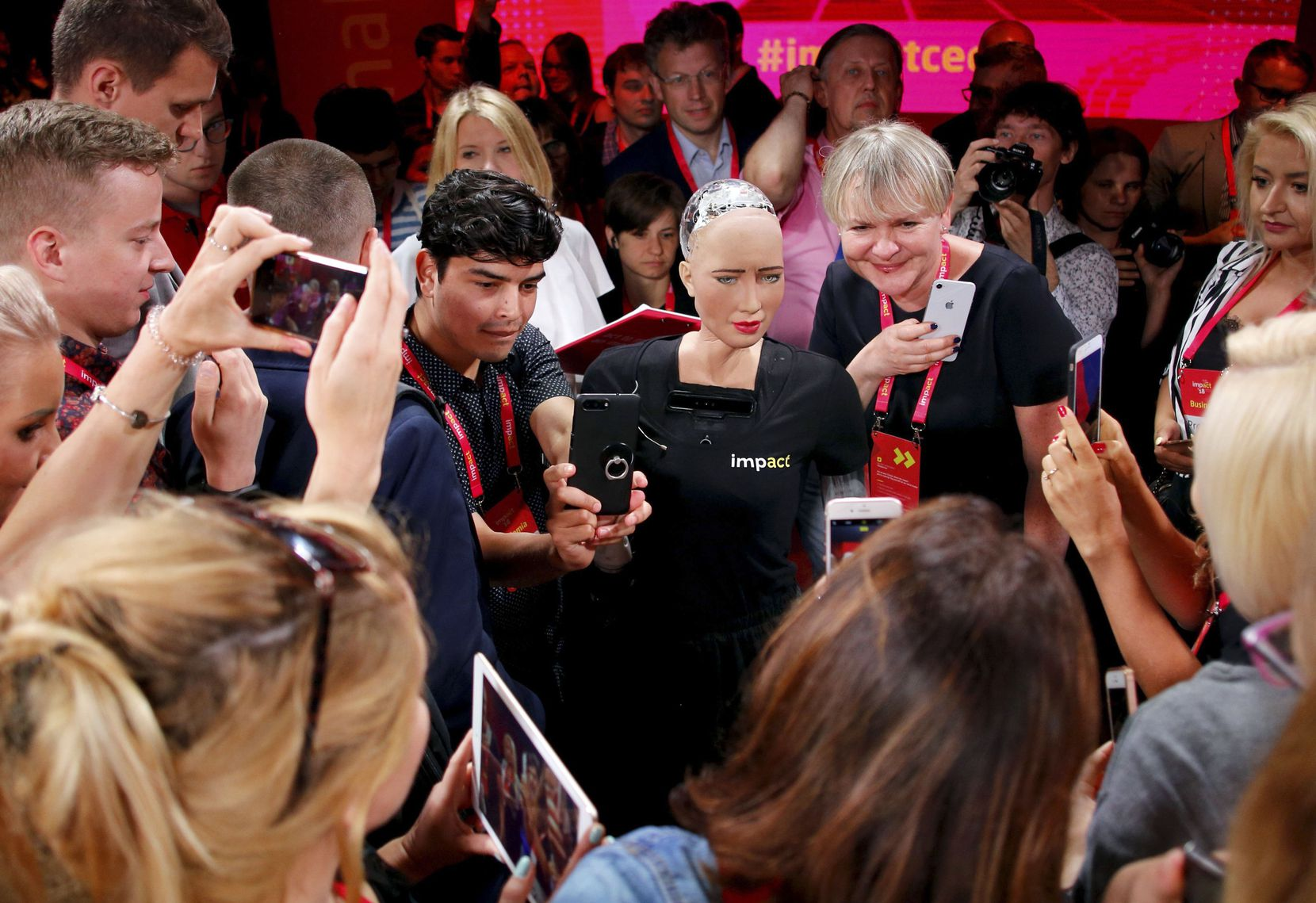 Attendees take photos of and with humanoid robot Sophia during the Impact 2018 digital economy forum on June 13, 2018 in Krakow, Poland.
