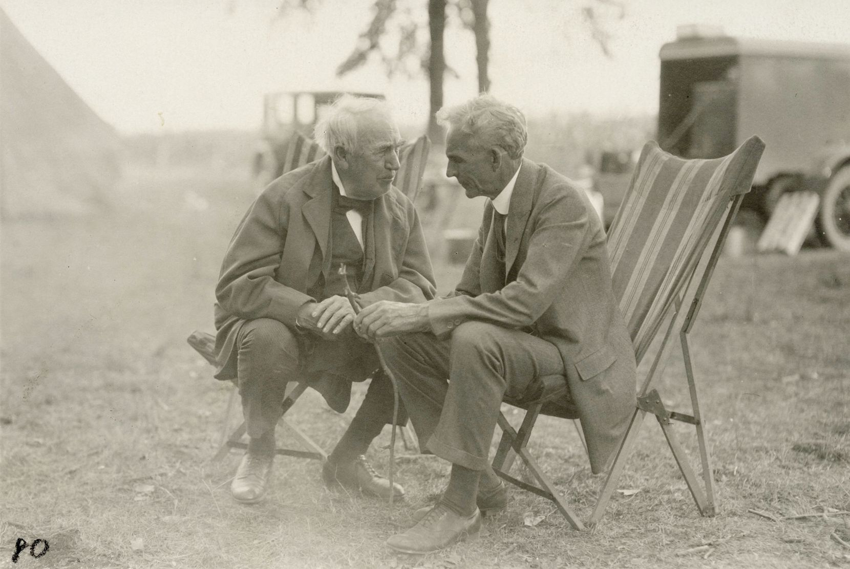 (From left) Thomas Edison and Henry Ford engage in discussion while at a campsite.