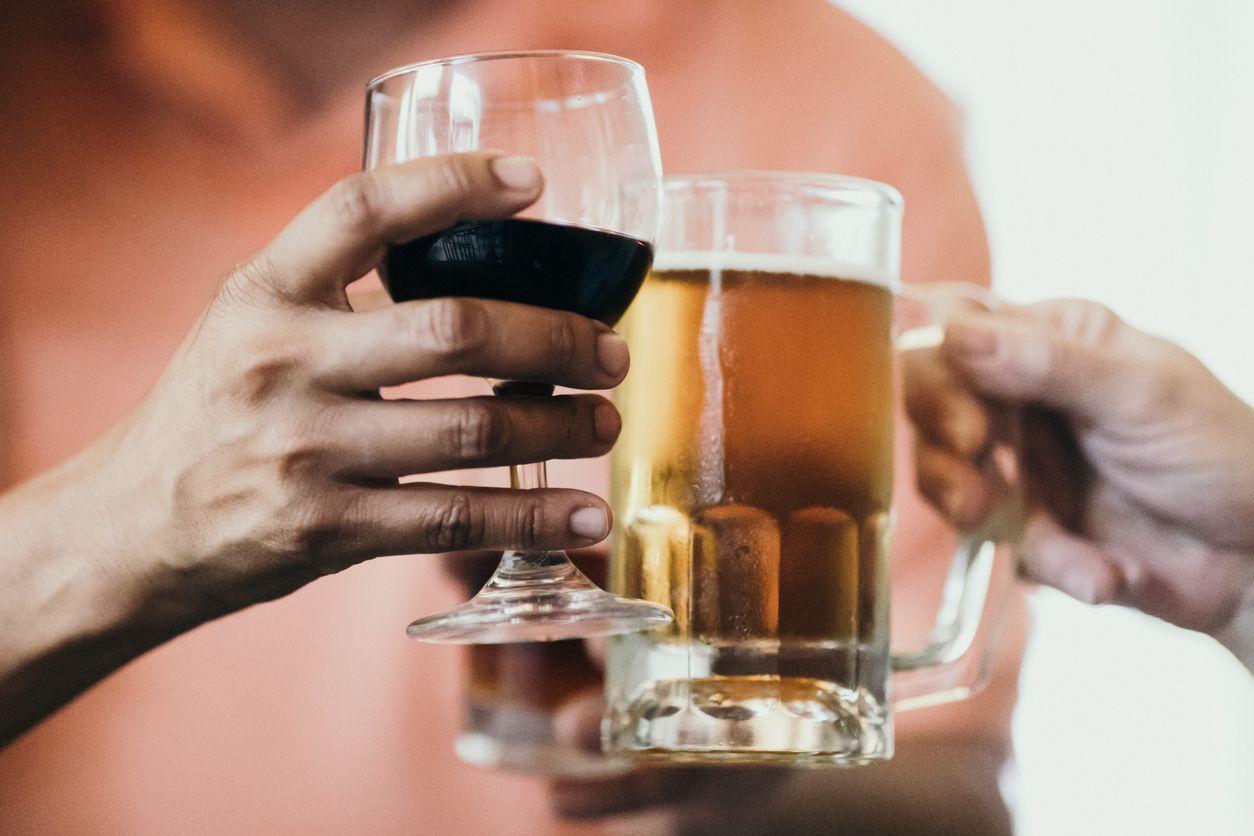 Dos personas brindan con una copa de vino y tarro de cerveza.